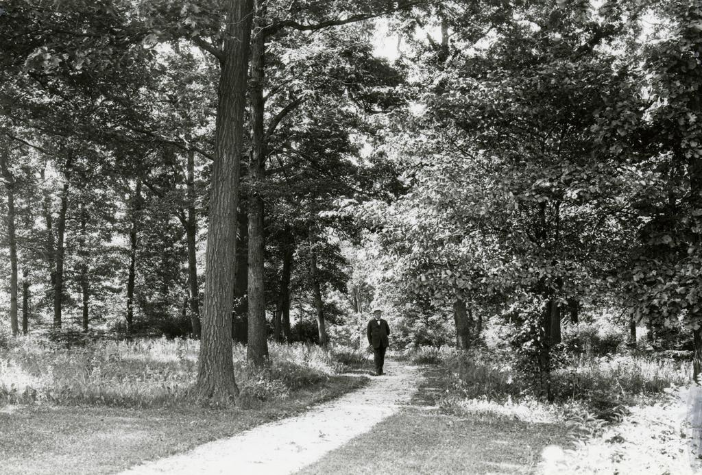 Black and gray photograph of Joy Morton standing on Joy Path. He is on a cleared trail and there are trees surrounding him.