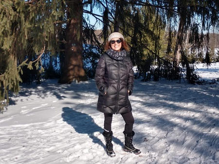 Anne Klos standing in a grove of snow covered trees