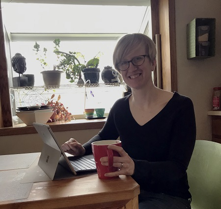 Carissa Dougherty sitting by a computer, with a cup in hand, smiling and in front of a window with plants.