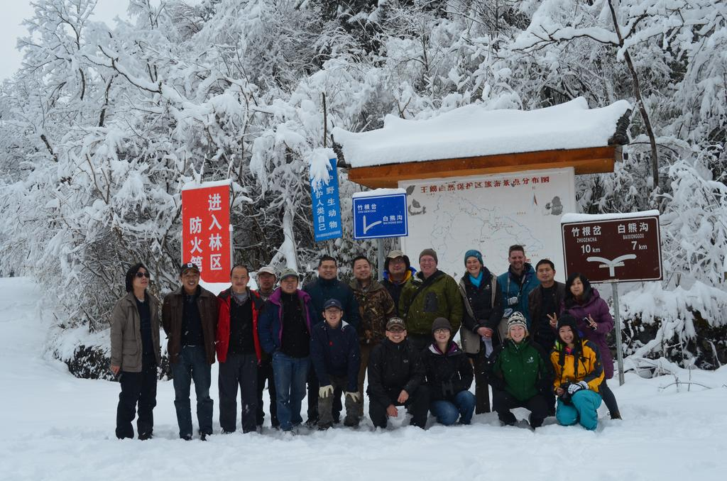 A group of adult men and women standing in the snow in a forest in front of a sign that is written in Chinese.