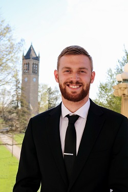 A portrait photo of Andrew Ernat in a suit and tie, with the Iowa State bell tower in the background