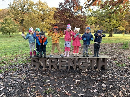 Children are dressed in their winter clothing and standing on a bench that says, strengh.