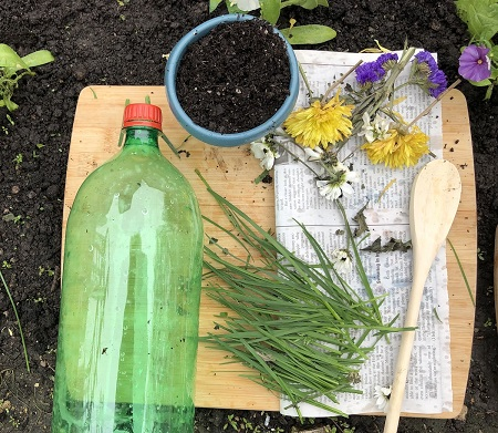 A plastic bottle, grass and flower cuttings and a pot of dirt are on a cutting board.