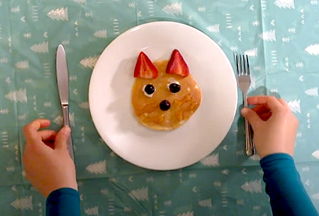 A pancake is made into the shape of a cat with strawberries for ears.