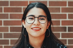 A head shot of Maddie Fernandez, with glasses, smiling in front of a red brick wall