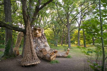 A giant wooden troll sits next to a tree, holding a rod with a net attached.