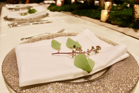 An elegant place setting with a napkin on a gold plate and budding sprig on top of the napkin