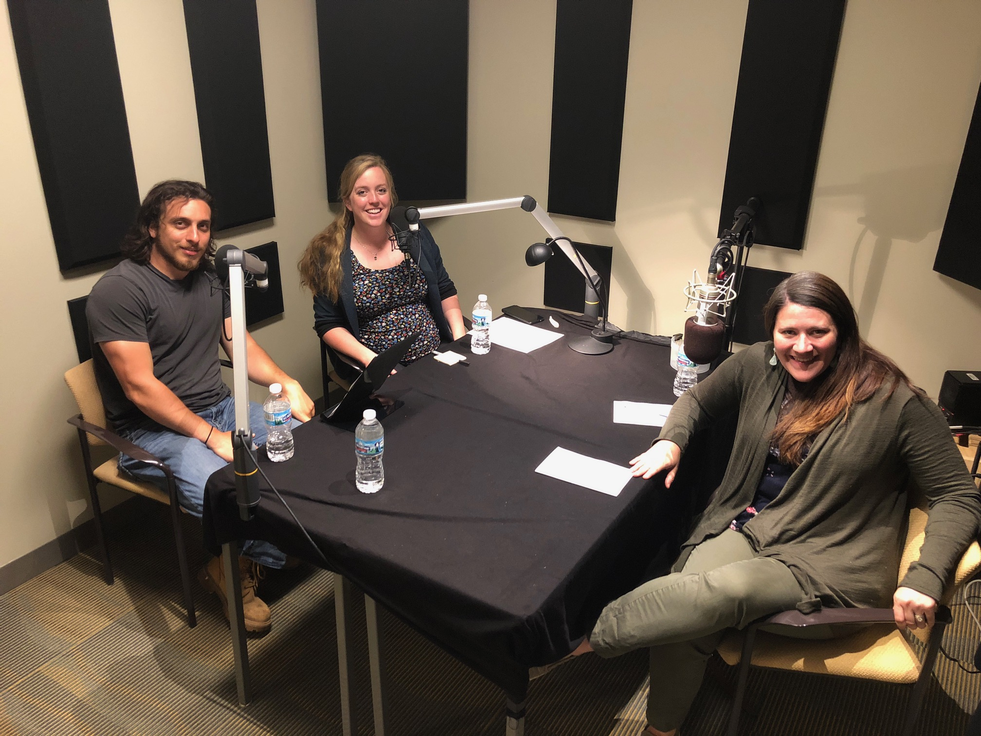 3 adults (2 female 1 male) sitting around a table in a recording booth with microphones