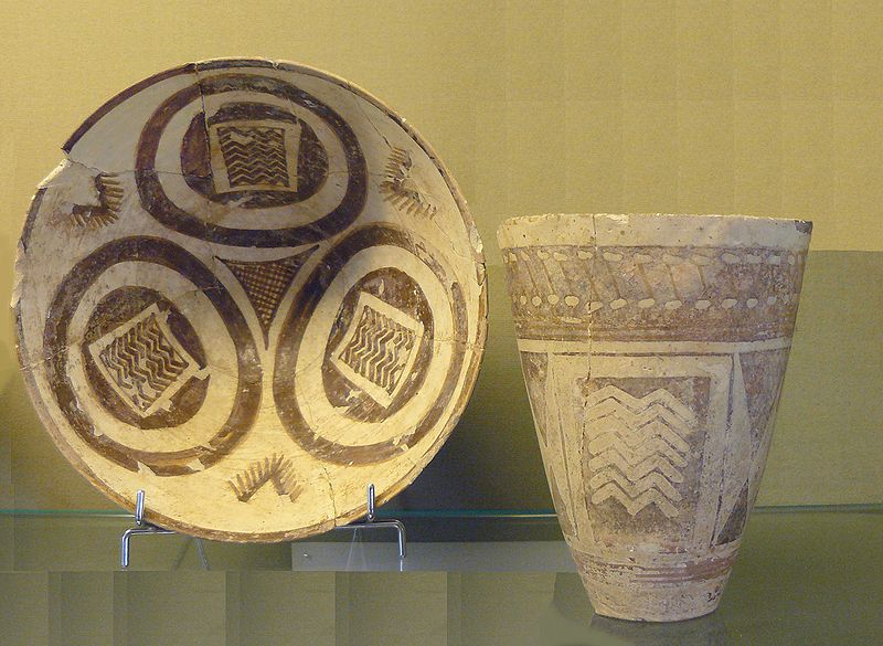 An ancient pot and vase. The pot and vase both look worn. They are tan with brown designs on them.
