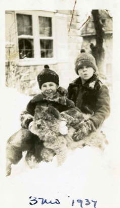 An old black and while photograph of Jean and Morton Lattner in the winter with a dog named Ming.