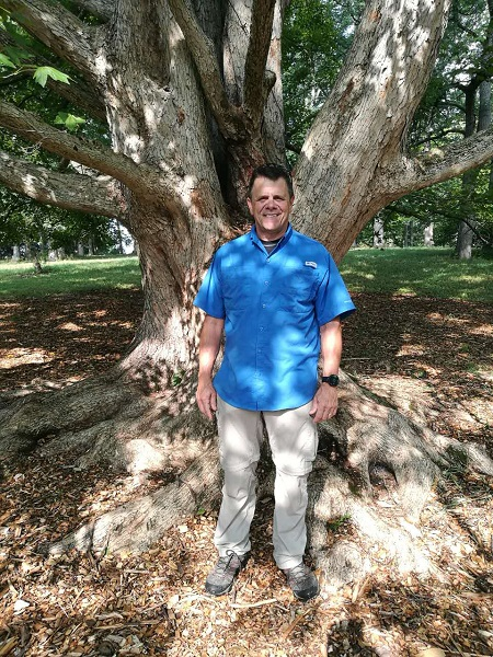 Kris Bachtell, smiling, standing in front of a State Street Miyabe maple tree