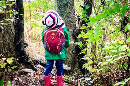 a child wearing a backpack and galoshes staring up at a tree