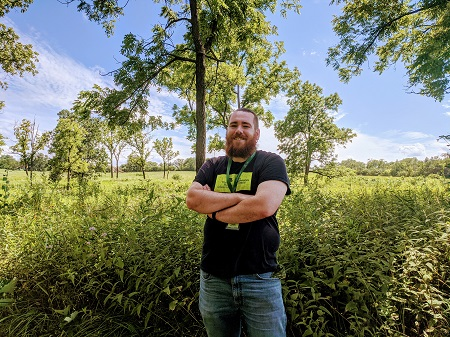 Daniel Neuffer standing with his hands crossed, smiling, in front of a landscape of trees