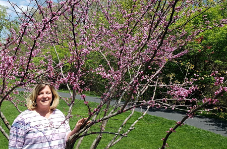 Peg Rurik standing by a blooming redbud tree