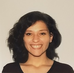 A head shot of Tanya Perez, smiling, in front of a tan wall