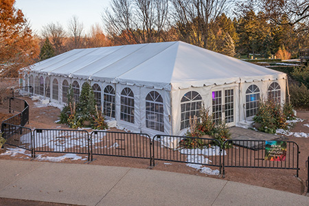 Exterior of Arbor Court tent flanked by lit planters with evergreens