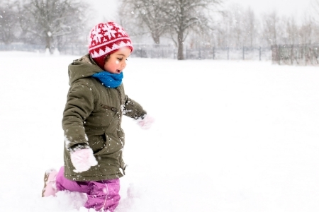 Little girl runs through the snow in a green jacket