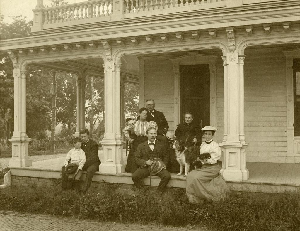 Black and white photograph of the Morton family seated on porch outside of Arbor Lodge