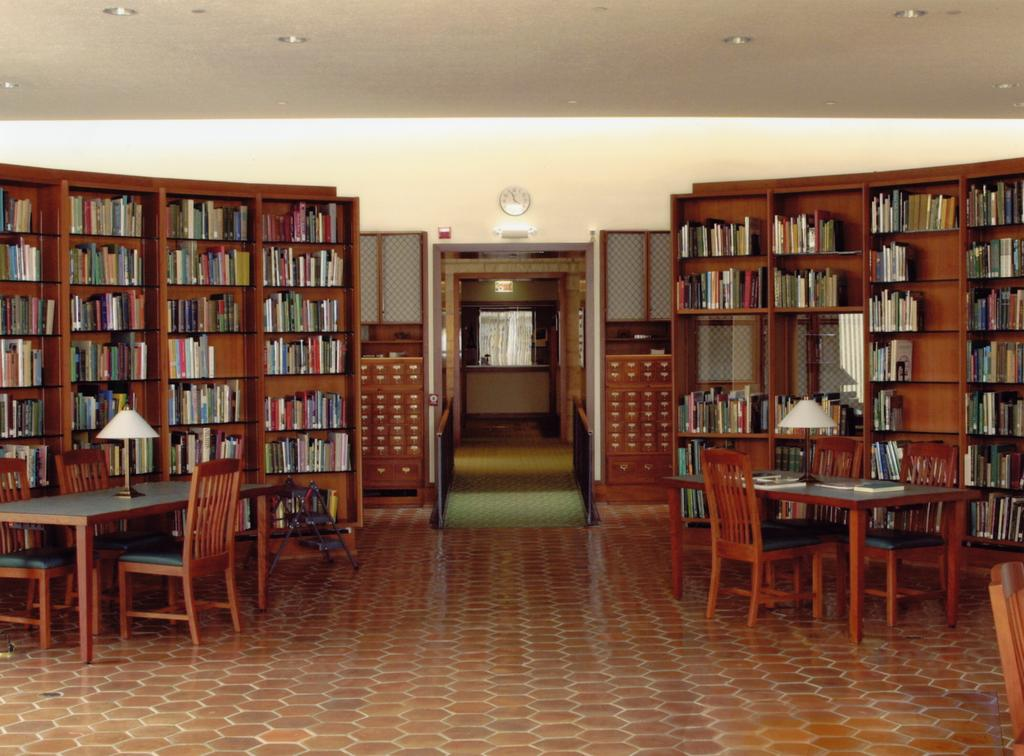 A color photograph depicting the rounded shelves with books on them, center of the library with tables, and the exit of the Sterling Morton Library.