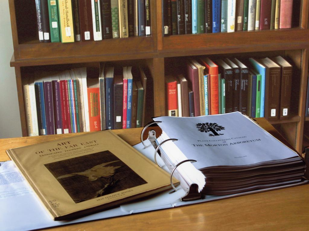 An open binder exhibiting documents from the Sterling Morton Library's archive. In the background is a bookshelf filled with books.