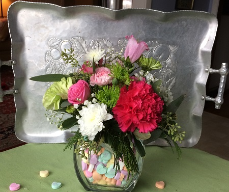 Carnations, roses and greens are arranged in a vase with heart candies.