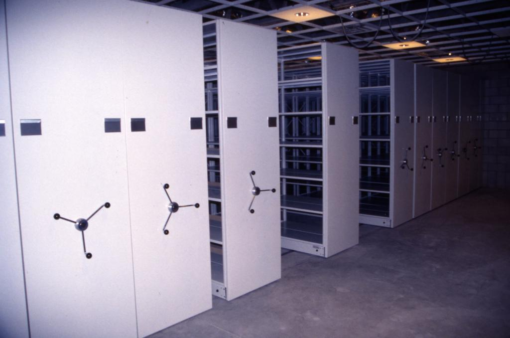 A photograph of white compacting shelving with materials on it. The remainder of the room has a cement floor and walls.