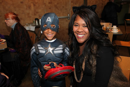 Visitor wearing cat ears on her son dressed in a super hero costume