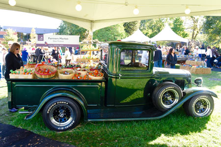 An old green pickup truck with  bushel baskets full of hand-blown glass pumpkins