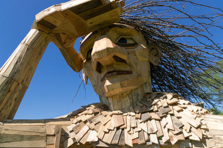 A troll, made of reclaimed wood, standing with one hand shading his eyes.