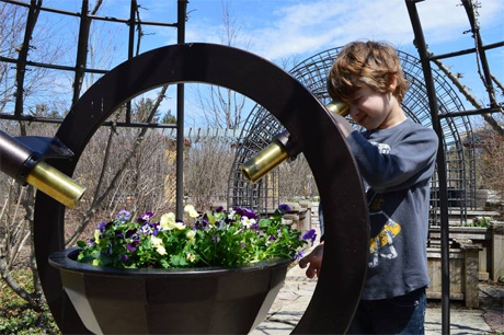 A child looking through a telescope at a pot of flowers