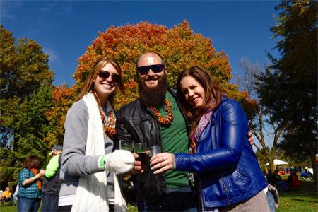 Visitors, wearing pretzels necklaces, enjoy cider samples
