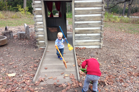 Children sweeping and raking leaves at the Mud Kitchen, a wood cabin