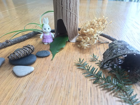 A small toy rabbit is surrounded by items found in nature and a paper tree.