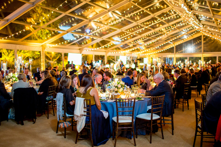 Tables of people eat dinner in a tent lit by strings of lights