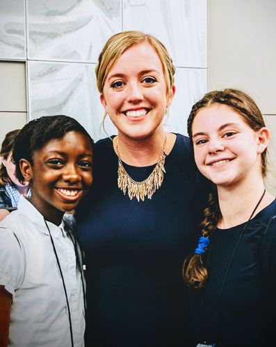 jessica turner-skoff stands with two children at an event