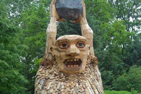 The troll made of reclaimed wood, is standing with his arms stretched over is head. He is holding a boulder in his hands. The troll stands about 15- 20 feet tall.