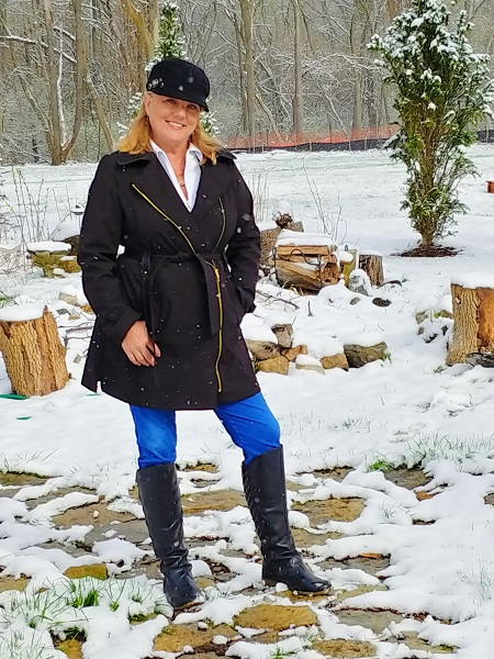 Kimberlee Puccio standing in her backyard surrounded by wood stumps and snow