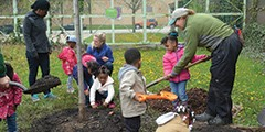 Kids and staff digging in a garden